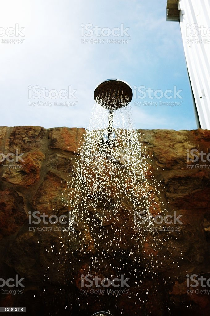 Water streaming down in  campsite outdoor shower stock photo