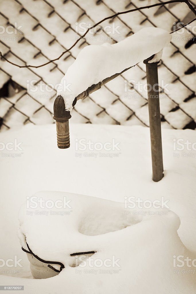 Water tap in the garden under  snow, sepia stock photo