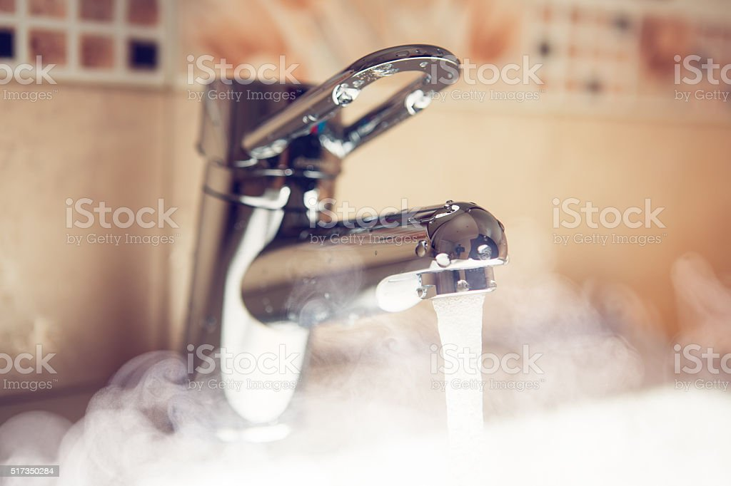water tap with hot water steam stock photo