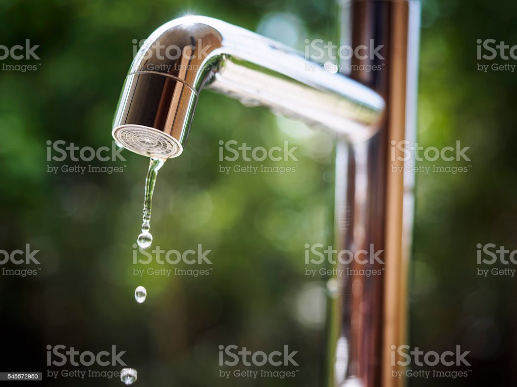 Water tap with water drop outdoor green park background stock photo