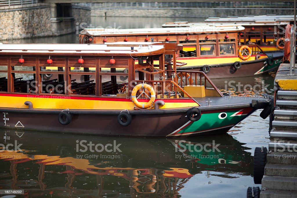 A water taxi rank with 3 long boats docked at it stock photo