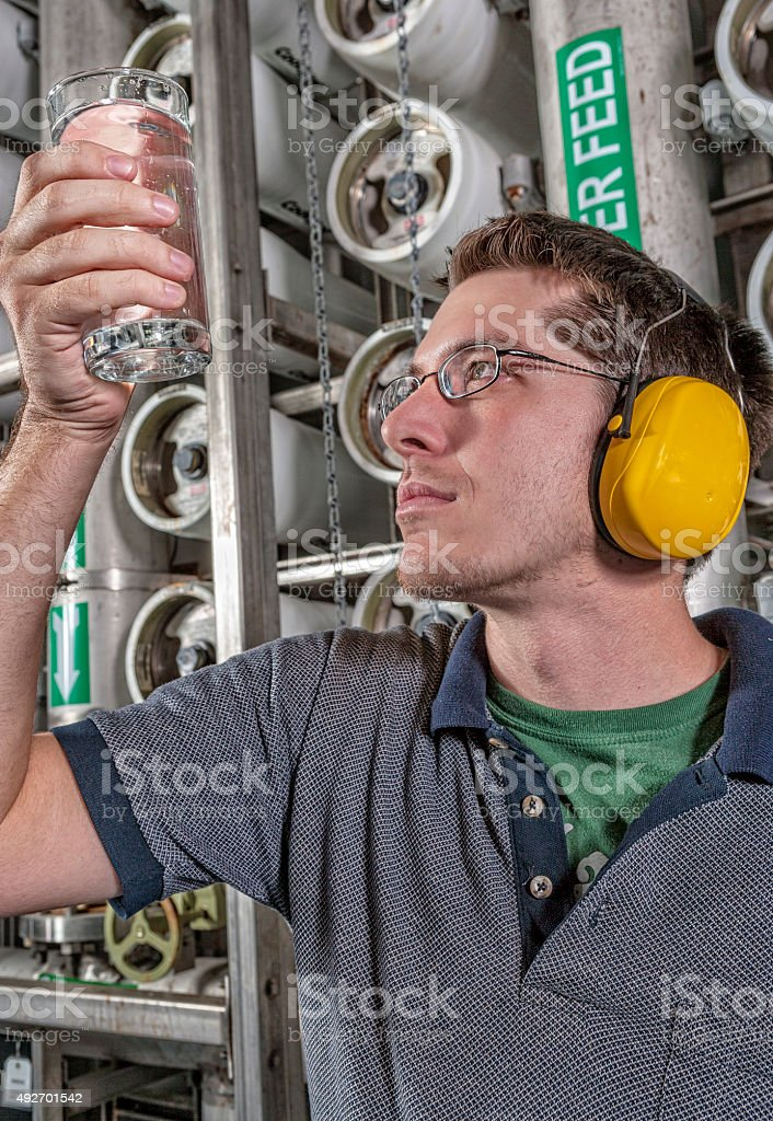 Water Technician Holds Up a Clean Glass of Water stock photo