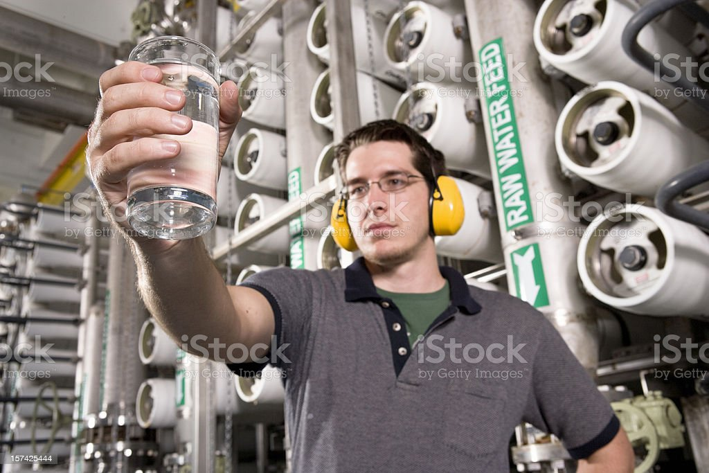 Water Technician Inspects Water at Public Utility Plant stock photo