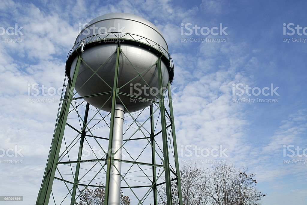 Water tower with green structure against sky stock photo