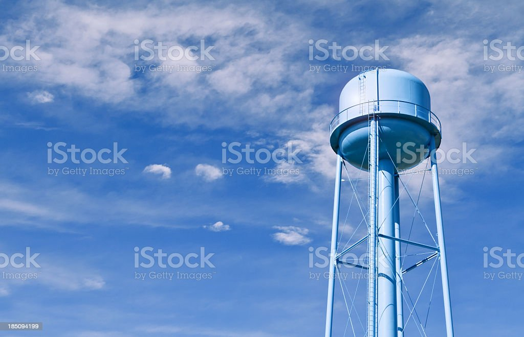 Water tower with wispy clouds in sky behind stock photo