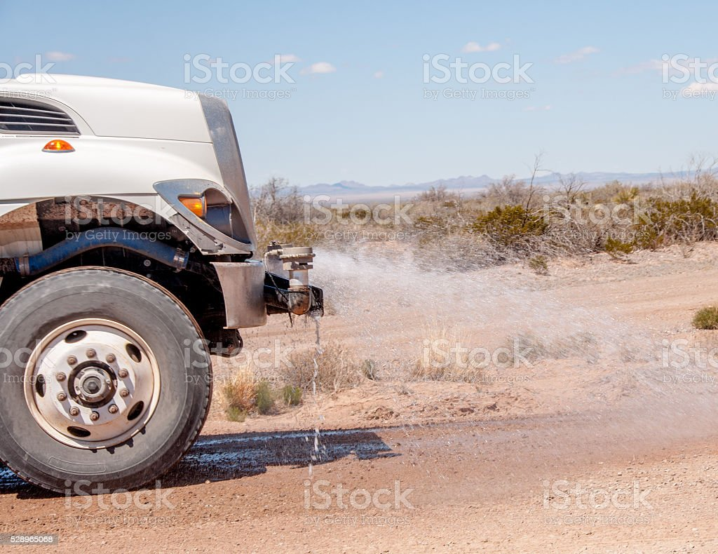Water Truck Controls Dust on Dirt Road stock photo