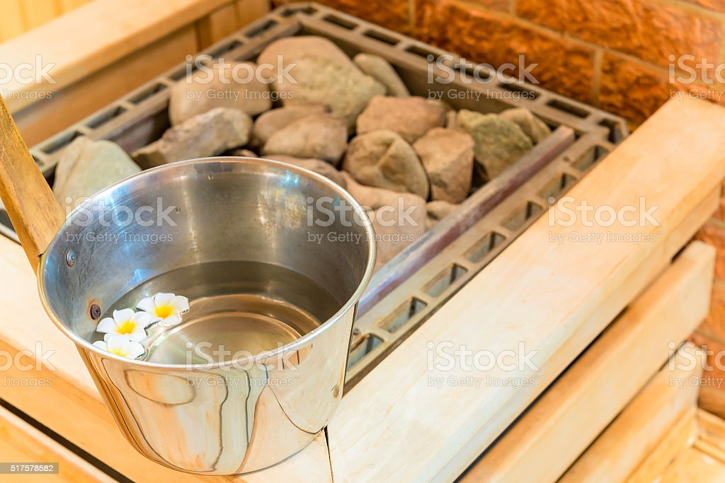 water with floating flowers and stones in the sauna stock photo