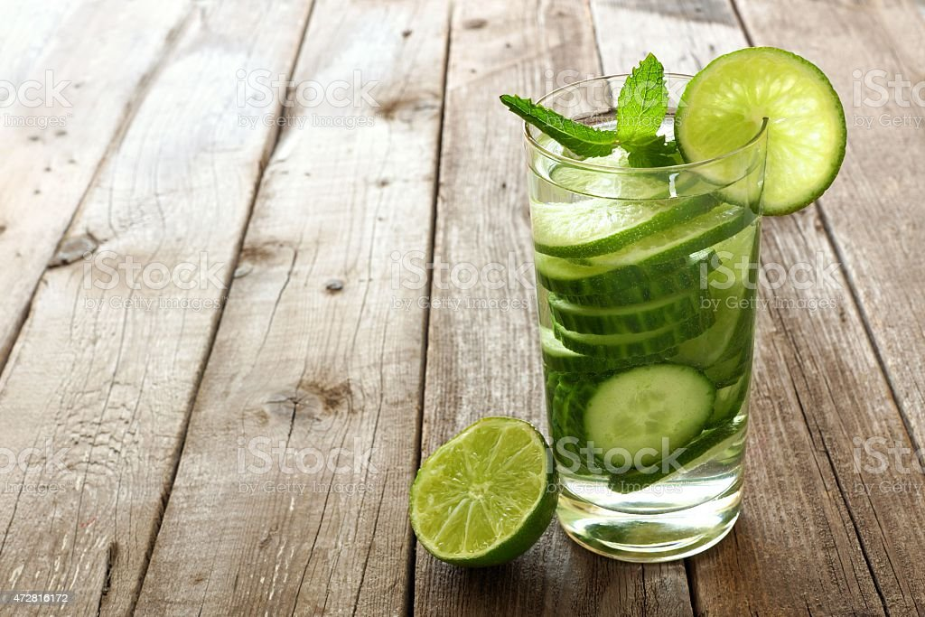 Water with lime and cucumber against wood stock photo