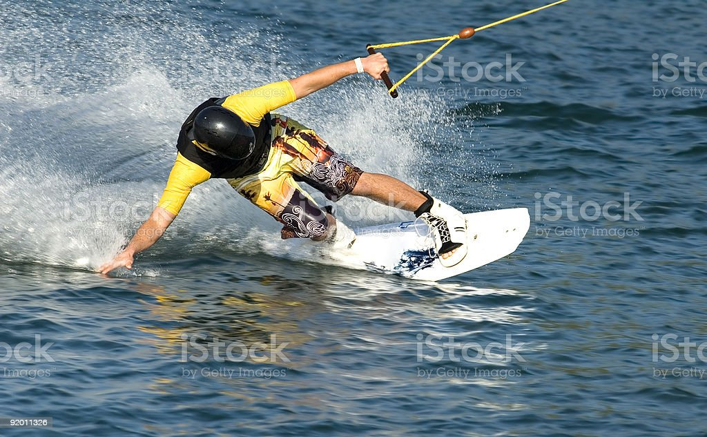 Waterboarder leaning down to touch the ocean stock photo