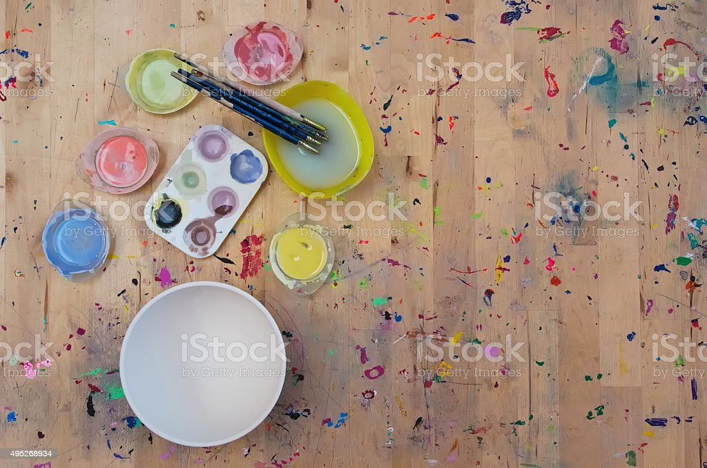 Watercolor paint, paintbrushes and a white bowl on light colored stock photo