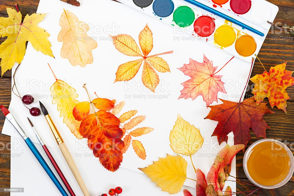 Watercolor painting with autumn leaves, paint, brushes and color stock photo