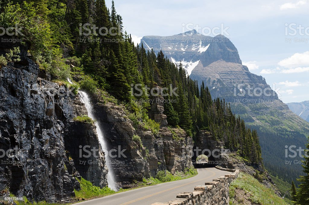 Waterfall and forest along road in Glacier National Park stock photo