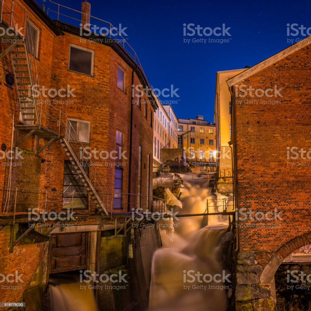 Waterfall and river between house walls stock photo