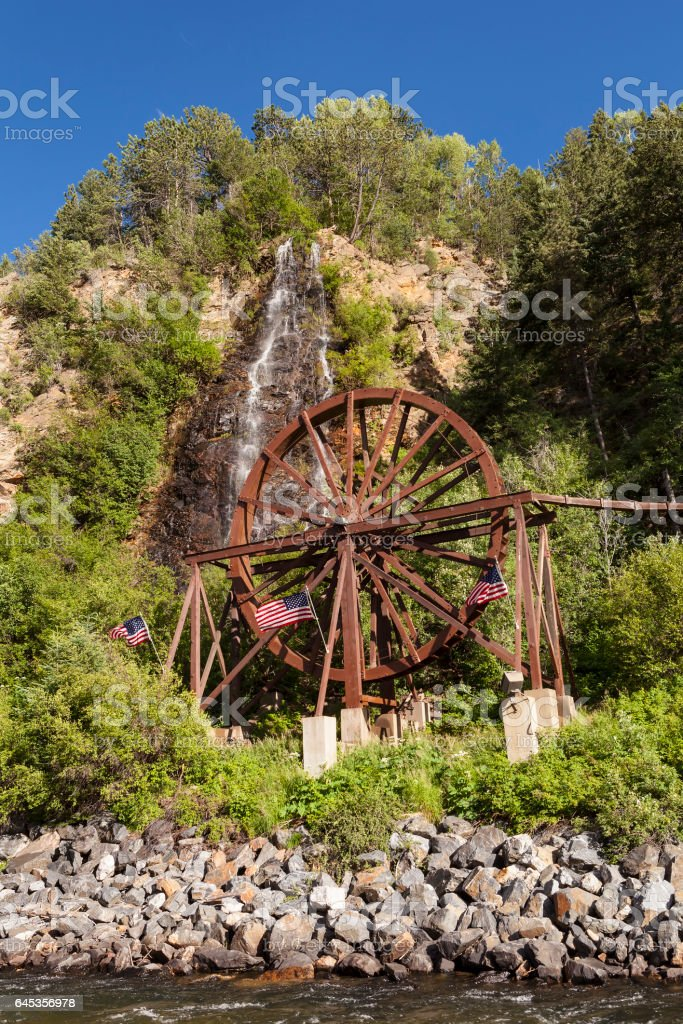 Waterfall and water wheel in Idaho Springs Colorado next to the I-70 Freeway. stock photo