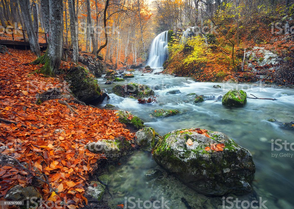 Waterfall at mountain river in autumn forest at sunset. stock photo