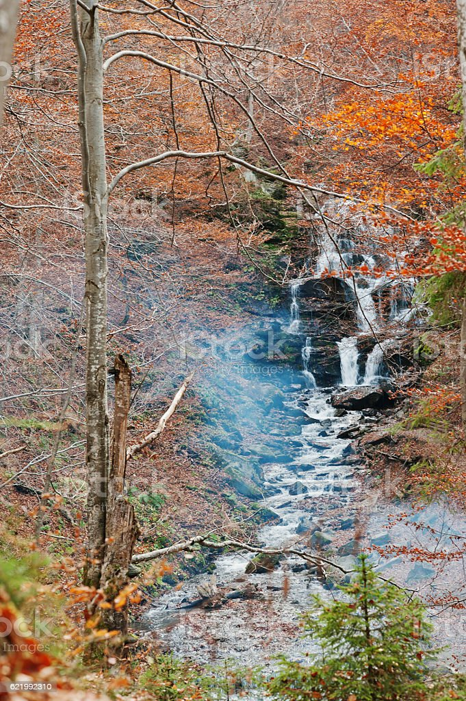 Waterfall Borzhava with smoke from fire under the mountain villa stock photo