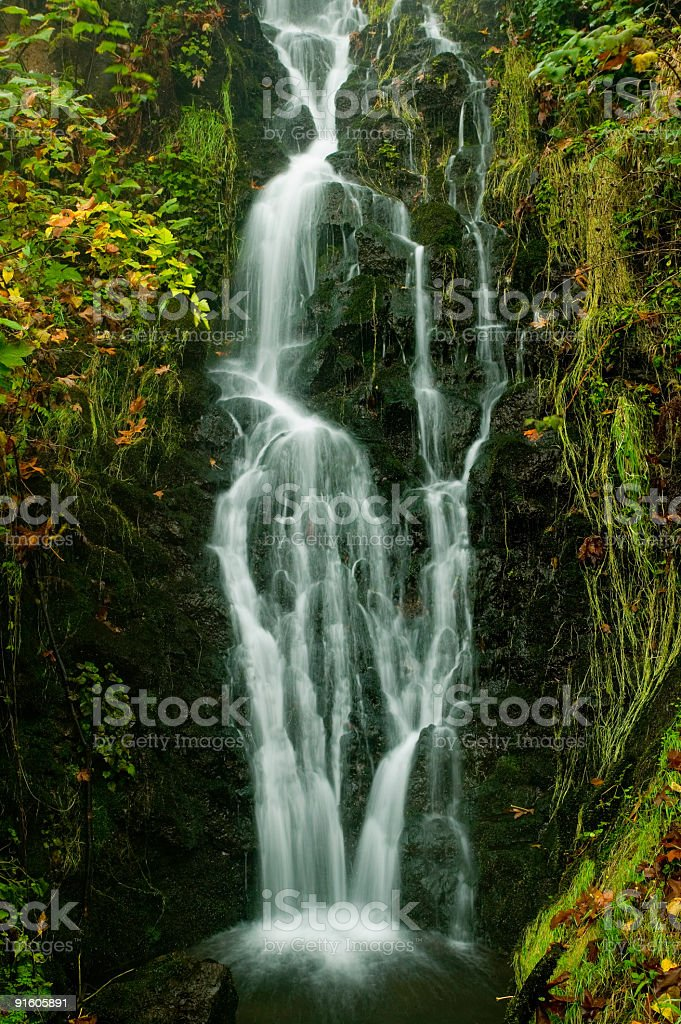 Waterfall cascades down rockface surrounded by fall colors royalty-free stock photo
