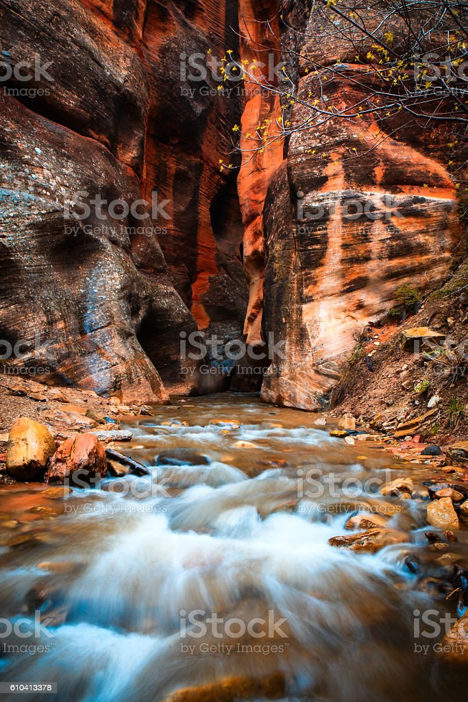 waterfall cascading out of a sandstone slot canyon stock photo