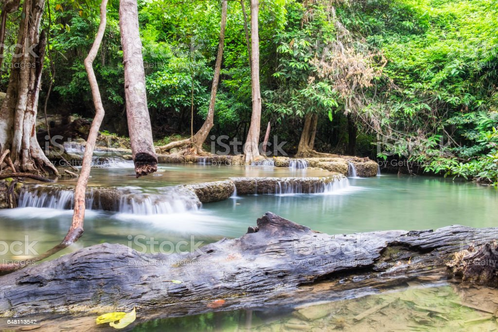 Waterfall flowing in tropical rainforest at huai mae khamin national park stock photo
