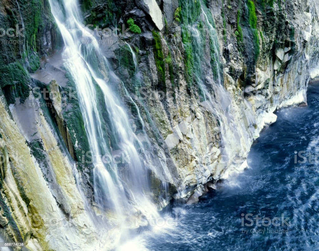 Waterfall flowing into the sea stock photo