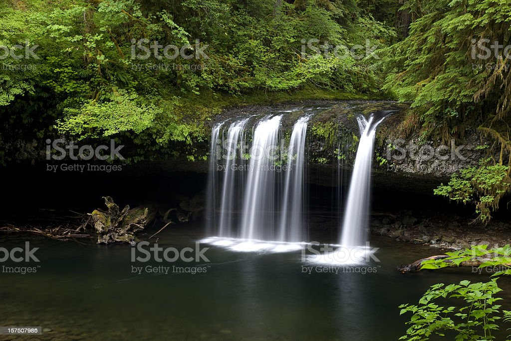 Waterfall flowing over columnar basalt outcropping into pool stock photo
