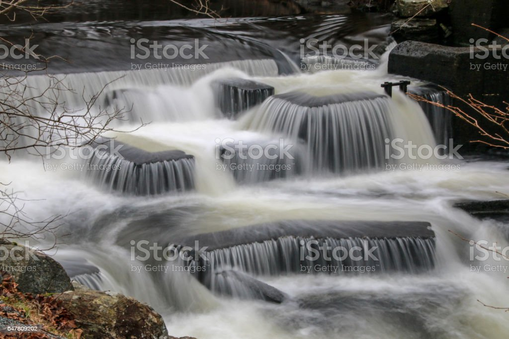 Waterfall formations in a river flowing down a fish ladder stock photo