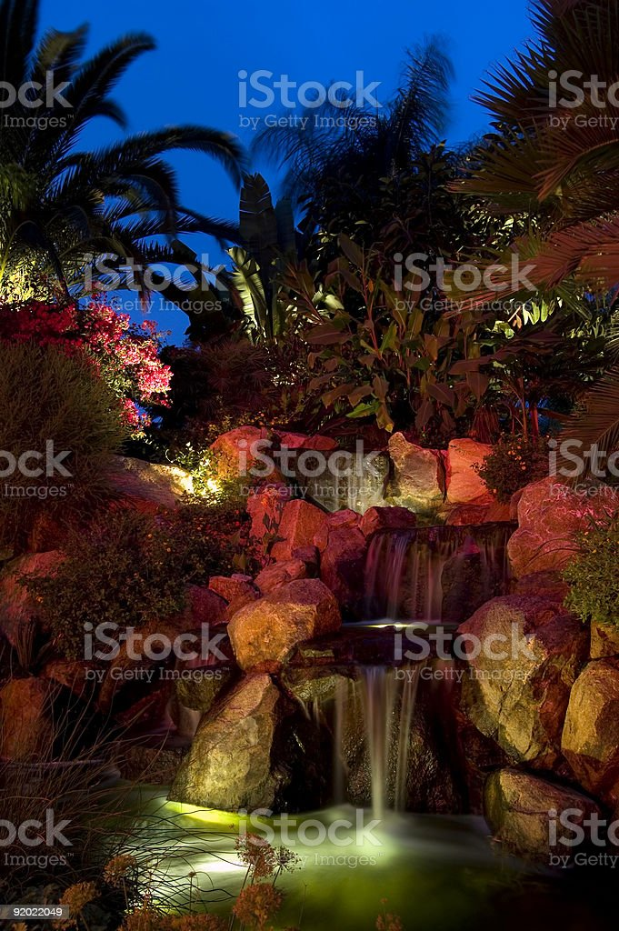Waterfall illuminated with colorful lights at night stock photo