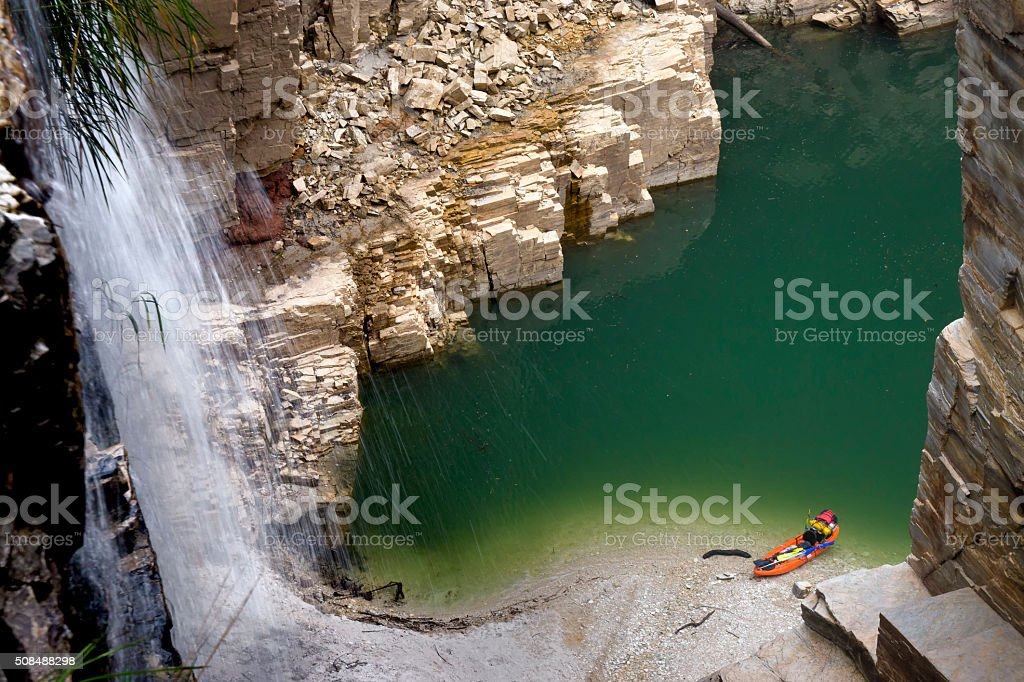 Waterfall in a canyon falling on a green water lake stock photo