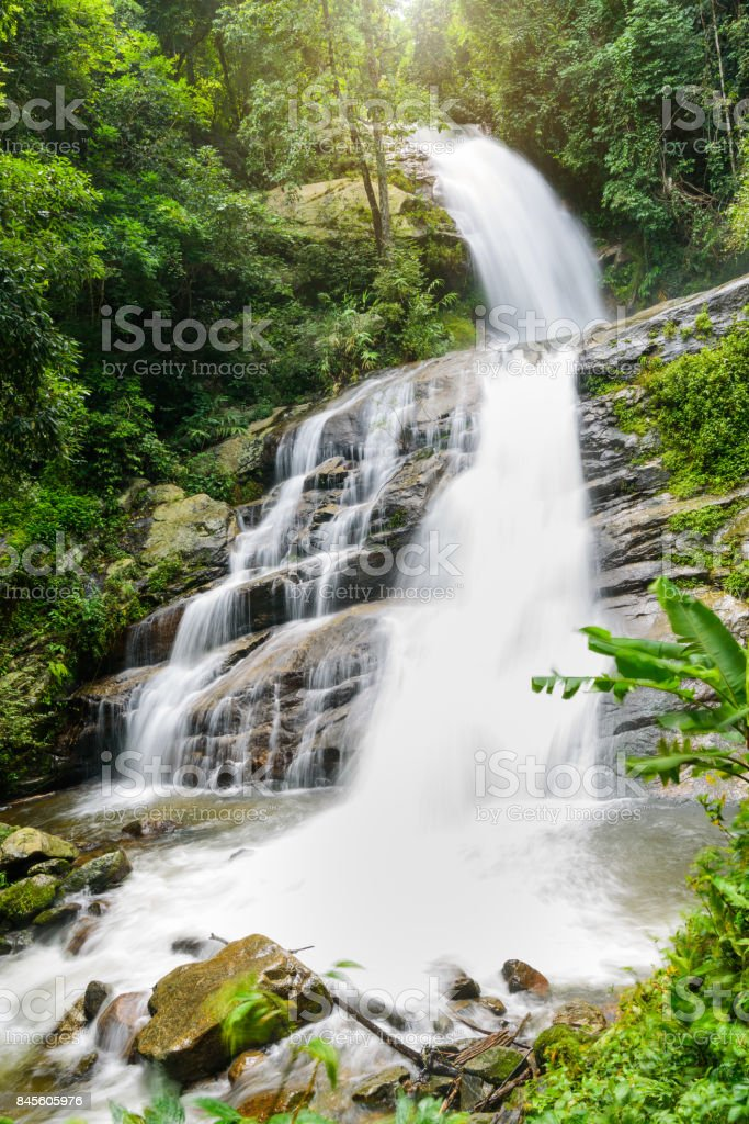 Waterfall in rain forest with flare of sun light at Mae Pan waterfall,Chiangmai, Thailand. stock photo