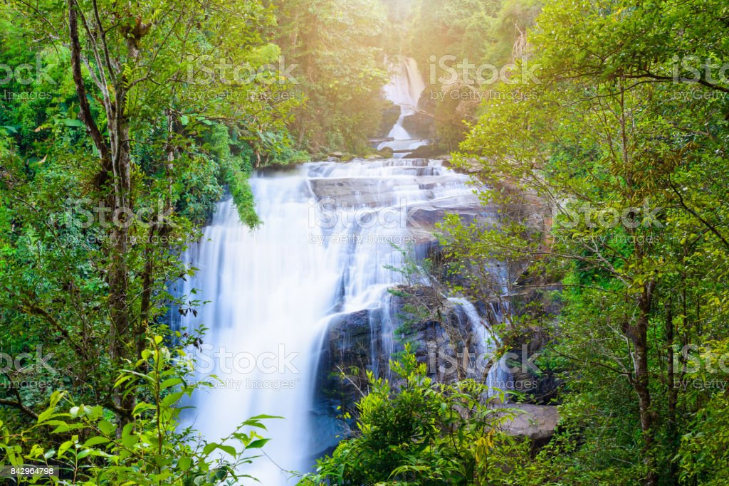 Waterfall in rain forest with flare of sun light at Sirithan waterfall,Chiangmai, Thailand. stock photo