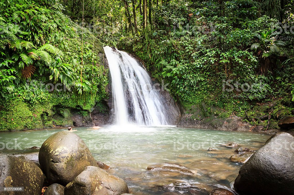 Waterfall in the forest with people stock photo