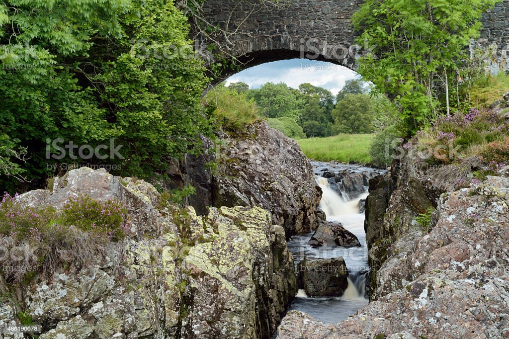 Waterfall on a Scottish river seen through arch of bridge stock photo