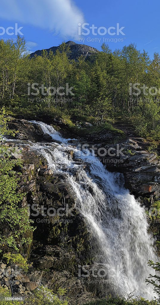 Waterfall on Risjok river and Kuelporr Mount in Khibiny Mountains stock photo
