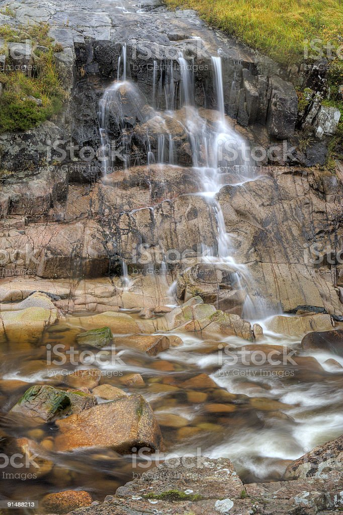 Waterfall over coloured rocks stock photo