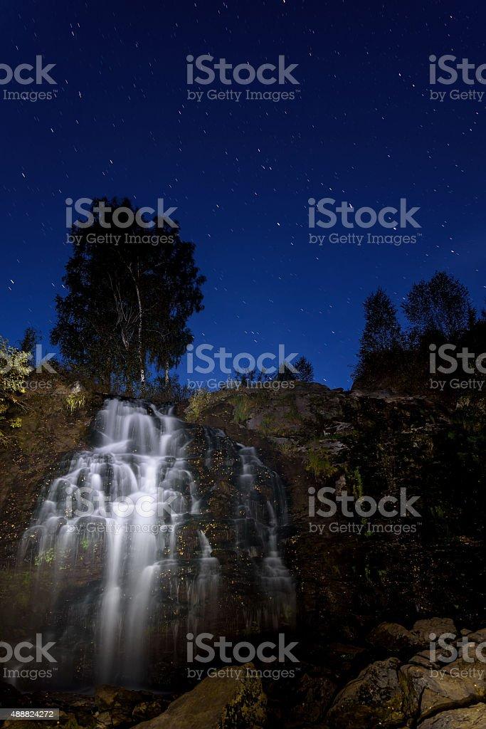 Beautiful night landscape with a waterfall illuminated among the...