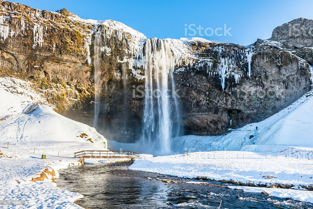 Waterfall Seljalandsfoss in winter, reflection in river. Iceland. stock photo