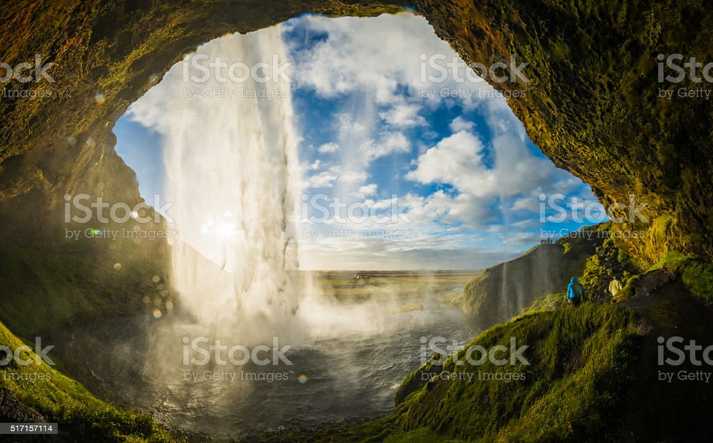 Waterfall tumbling into river above cavern mouth Seljalandsfoss Iceland stock photo
