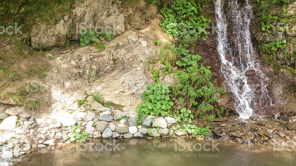 Waterfall which flows into the river stock photo