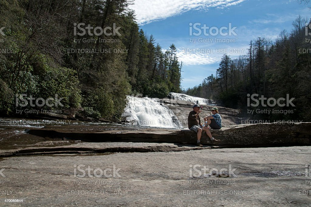 Waterfall with a couple talking stock photo