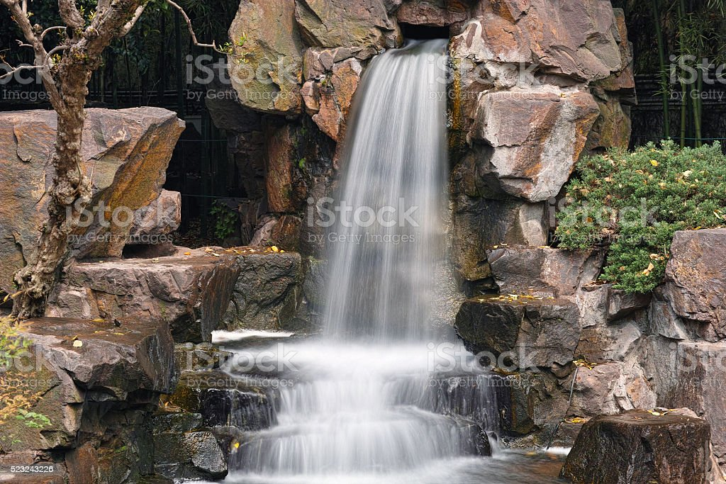 Waterfall with long shutter speed in park. stock photo