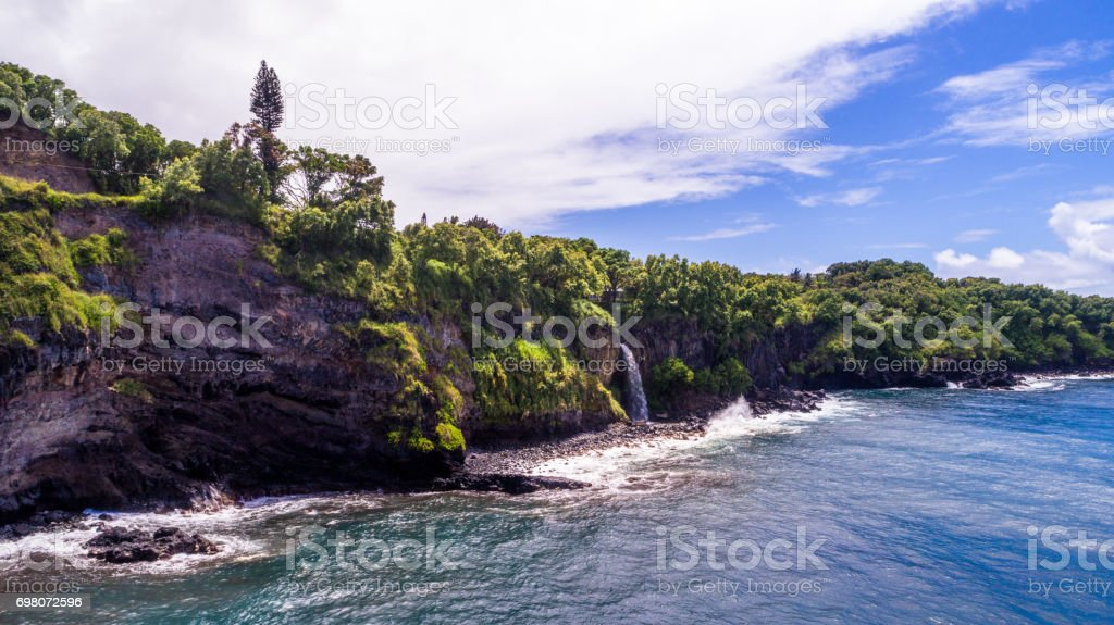 Waterfalls cascading down the cliffs over pasific ocean, Hawaii stock photo