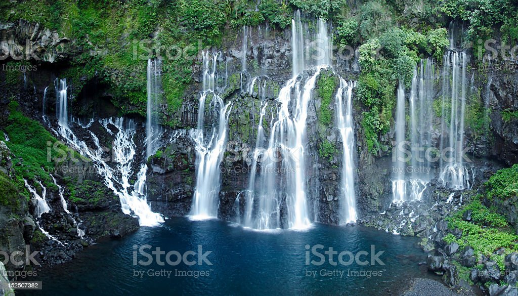 Waterfalls streaming into a clear blue lake stock photo