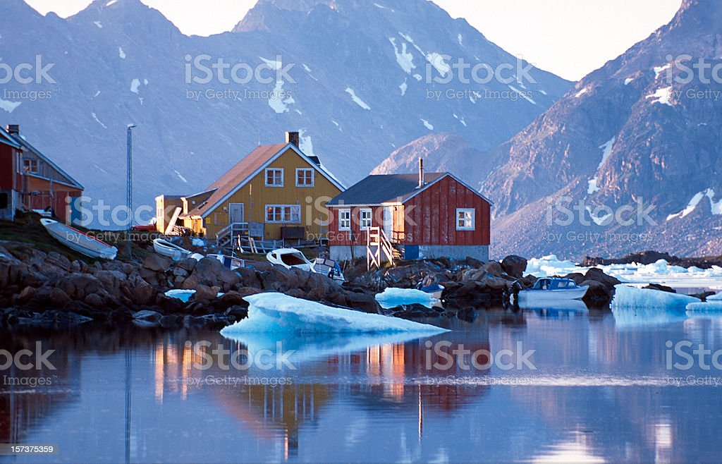 Waterfront homes in Greenland with mountains in background stock photo