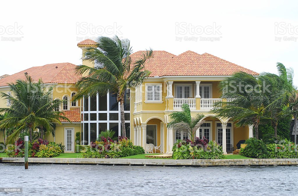 Waterfront mansion with palm trees stock photo