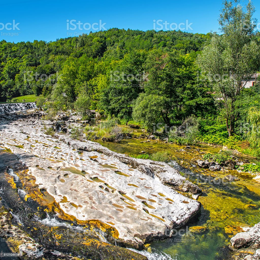 Waterhole from rock erosion in riverbed in middle of forest stock photo