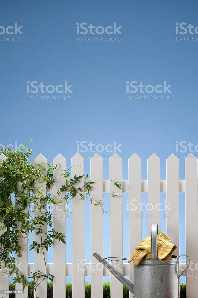 Watering Can And Gloves With White Fence royalty-free stock photo