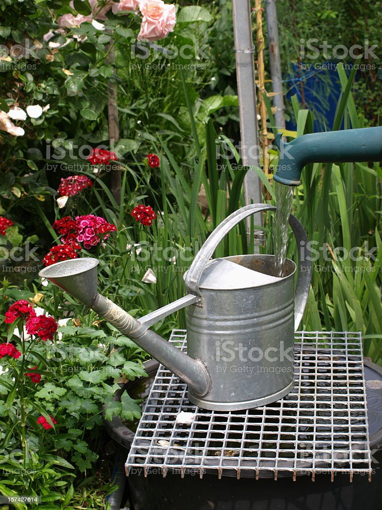 watering can at fountain stock photo