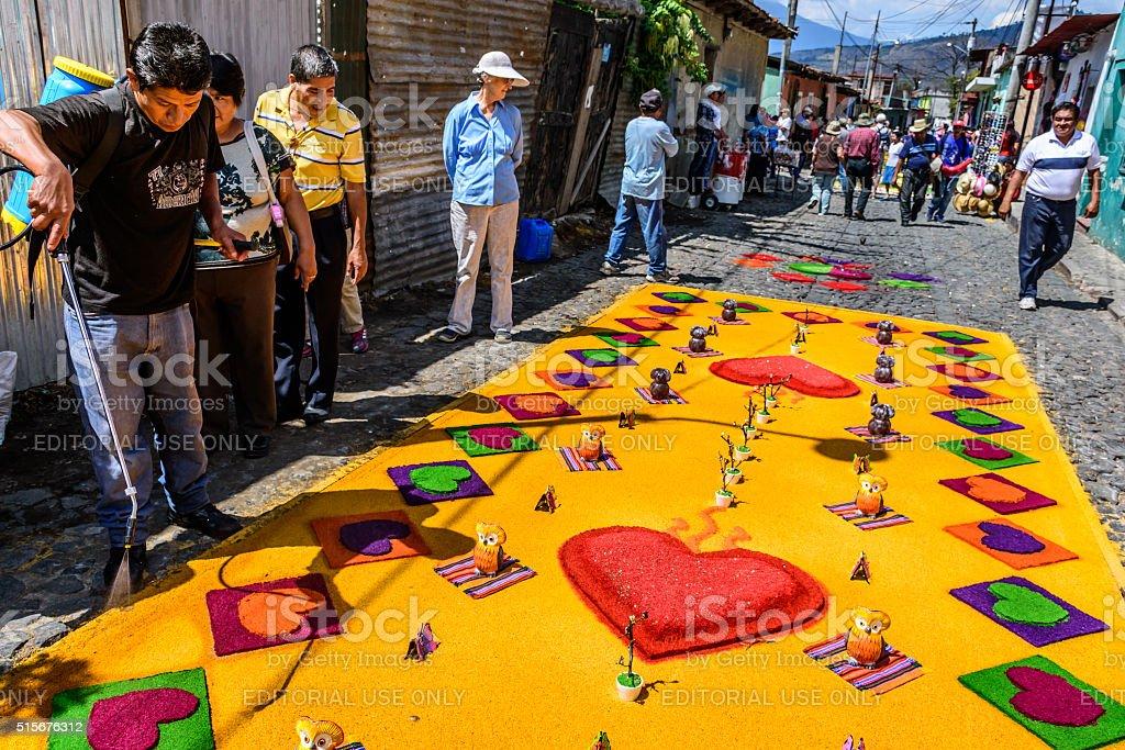 Watering colorful Lent carpet of hearts, Antigua, Guatemala stock photo