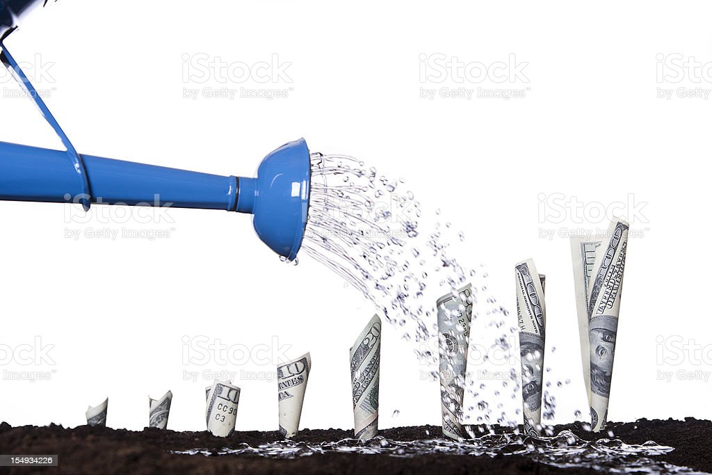 Watering Money to Make it Grow stock photo