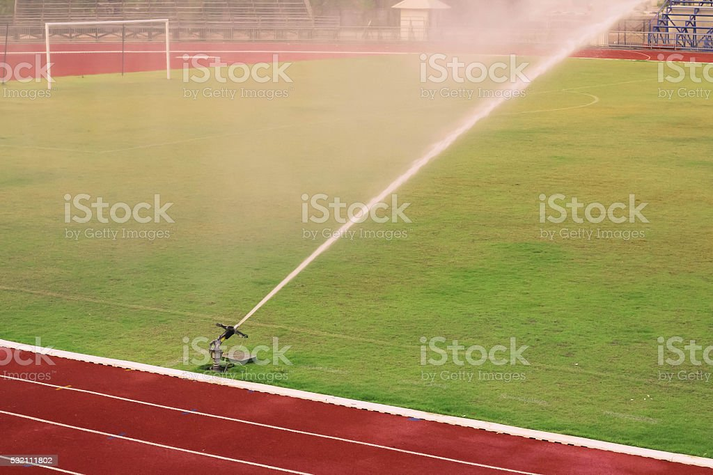 Watering the football field stock photo